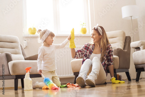 Foto Murales Daughter and mother cleaning home together and having fun.