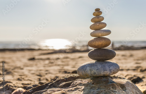 Plexiglas Zen Stenen Pyramid of stones on the beach in the end of evening