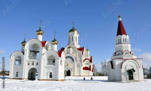 zbliżenie śnieżnobiały Kościół z dzwonnicą. W zimie Słoneczna pogoda, kopuły świątyni wyróżniają się pięknie na błękitnym niebie. Świątynia otoczona jest zimowym krajobrazem i białym śniegiem.