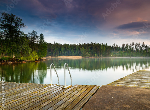Aluminium Pier jetty with ladder at a little lake with forest around