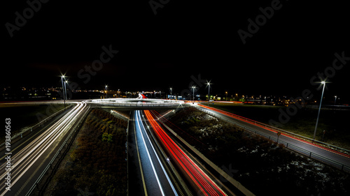 Fotobehang Nacht snelweg light trails for cars passing a roundabout and roadside sides