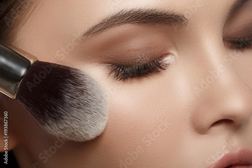 Close up of female eye area. Young woman putting on powder on face. Macro concept