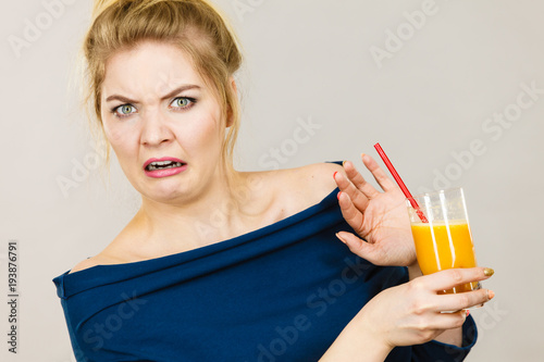 Foto op Canvas Sap Disgusted woman holding orange juice