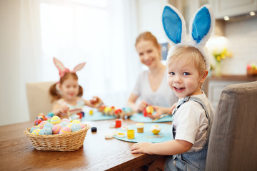 Happy easter! family mother and children paint eggs for   holiday