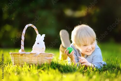 Charming little boy hunting for easter egg in spring park on Easter day