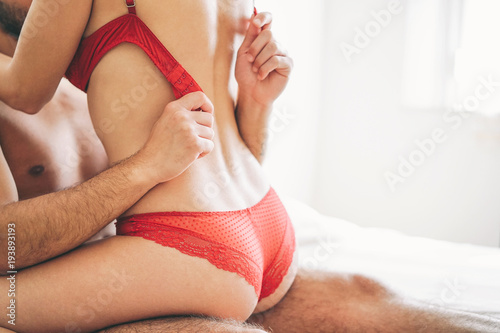 Beautiful passionate young couple having sex on the bed at home - Intimate and sensual moments of a couple making love in the bedroom - Sexual and erotic concept - Vintage filter - Focus on male hand
