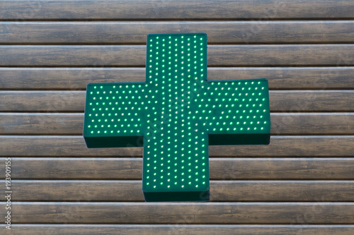 Fotobehang Apotheek Neon green cross sign on wooden background