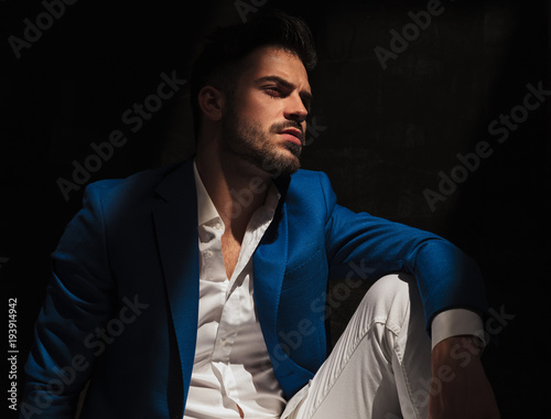 side view of a dramatic man sitting in studio