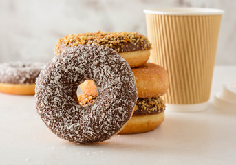 Paper cup of coffee with tasty donuts on white background.