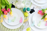 Beautiful table setting with crockery and flowers for Easter celebration