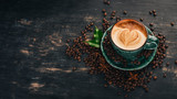 A fragrant cup of coffee Cappuccino on a black wooden background. Top view. Copy space.