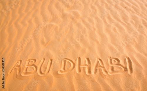 Fotobehang Abu Dhabi Abu Dhabi handwritten text in desert sand.