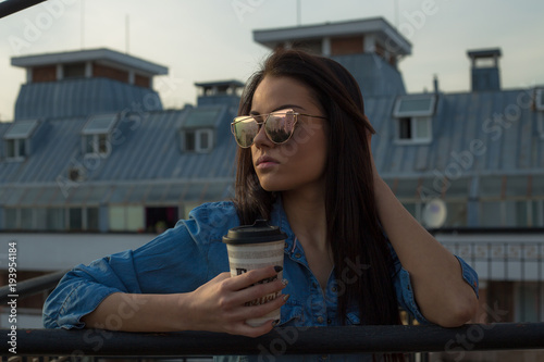 Young woman holding coffee cup on balcony