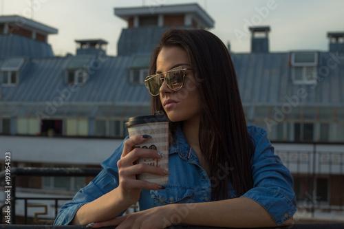 Młoda kobieta trzyma filiżankę na balkonie