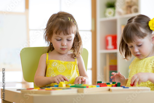 Kids play educational toys in kindergarten or daycare