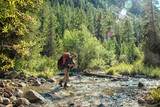Hiker with backpack crossing mountain river. Hiking river crossing on the stones.