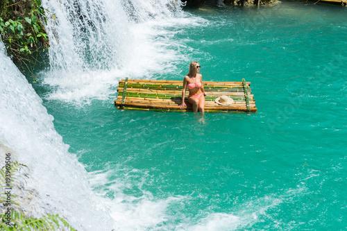 Woman in bikini sitting on bamboo raft close to waterfall. - 193969506