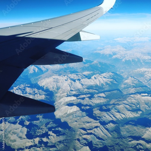 View from airplane flying over Alps mountains