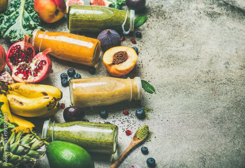 Fototapeta Colorful smoothies in bottles with fresh tropical fruit and superfood on grey concrete background, selective focus, copy space. Healthy, vegetarian, detox, dieting, clean eating breakfast food concept