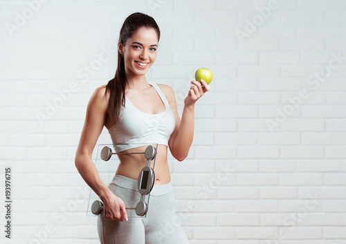 Piękny, sprawny, młoda kobieta trzyma skalę wagi, nad białym murem