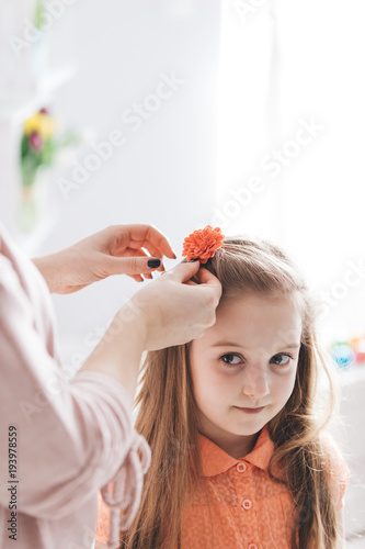Foto op Aluminium Kapsalon Mother clipping a hair clip with red flower