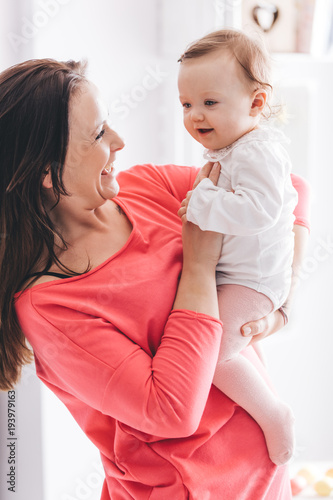 Young woman holding a baby girl on her hands