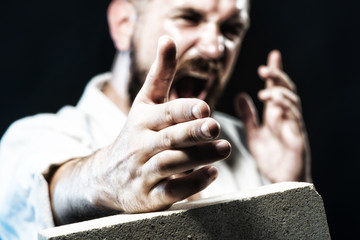 Strong, focused professional karate instructor training in judo, taekwondo, aikido. Karate man breaking with hand concrete brick. Karate man in action. MMA - Mixed martial art. Selective focus on hand