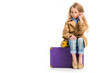 Stylish kid in glasses wearing trench coat and sitting on suitcase isolated on white