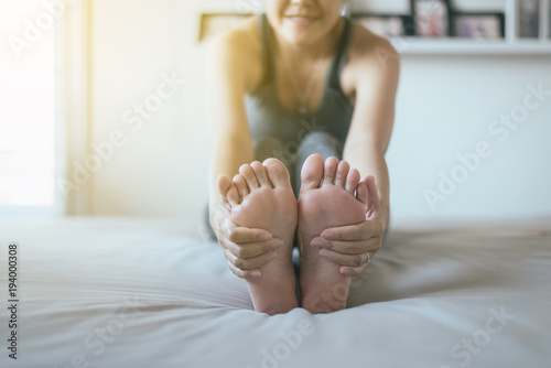 Plakat Happy woman sitting on bed practicing doing yoga exercise,workout after waking up at home,Healthy and  lifestyle concept