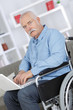 mature man in a wheelchair working on a laptop