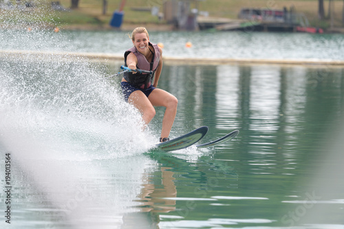 Woman water skiing one handed