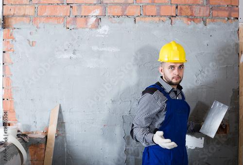 Man in the helmet ready is plastering the wall © JackF
