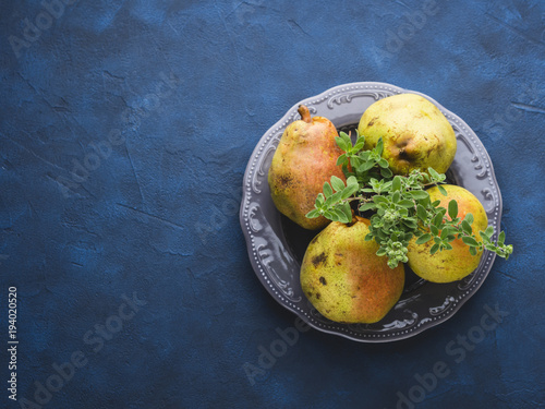 Italian pears and herbs on a gray dish over blue concrete background - 194020520