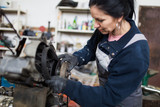 Strong and worthy woman doing hard job in car and motorcycle repair shop. - 194025988