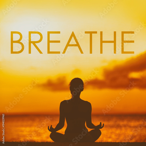 Leinwanddruck Bild BREATHE yoga inspirational title on sunset beach background woman meditating in lotus pose yoga meditation at sunset. Word breathe written on copy space for motivation in health and fitness concepts.