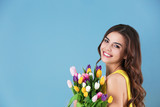 Beautiful woman holding bouquet of tulips on color background - 194046310