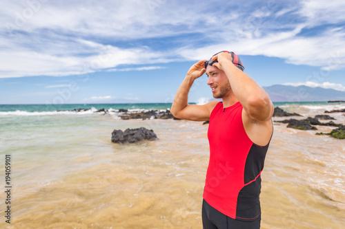 Man triathlete swimmer putting on swim goggles - Triathlon sport athlete going swimming getting ready an ocean swim. Fit man in professional triathlon suit training for ironman.