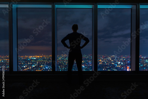 Man looking out large windows high above a sprawling city at night - 194060752