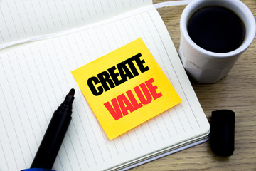 Hand writing text caption inspiration showing Create Value. Business concept for Creating Motivation written on sticky note paper, Wooden background with space, Coffee and marker © Artur