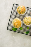 Savory muffins with feta cheese and spinach on a wire rack on a wire rack.White stone backdrop. - 194064989