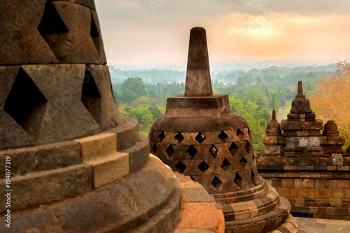 Foto op Aluminium Boeddha Huge stone Buddhist stupas against the background of the sunrise in the Borobudur Temple. Java island. Indonesia. Famous historical place. Outside.