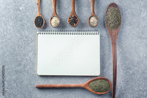Aluminium Kruiden 2 Notebook and spoons with different spices on grey background. Cooking master classes