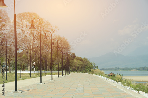 Different lighting/The walkway has a lighted pillar. There are deciduous trees and blue sky in the background, flares, sunlight, light from the light. All the brightness and beauty are different,