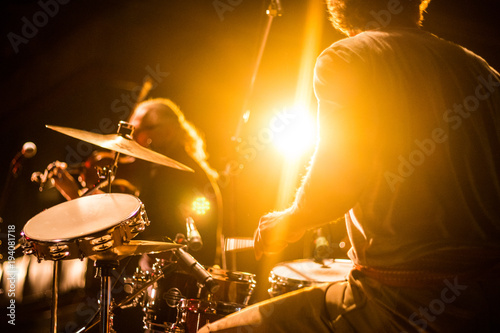 Drummer on stage playing with a band with gold yellow light shining in background  - 194081718