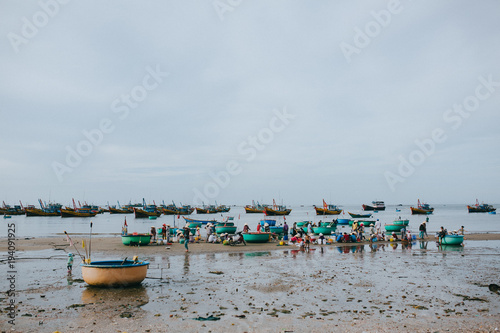 MUI NE, VIETNAM - 03 JANUARY, 2018: vietnamese fishermen with seafood on sandy beach at Mui Ne, Vietnam