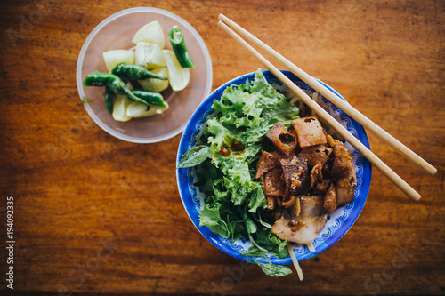top view of delicious vietnamese food in bowls with chopsticks on wooden table
