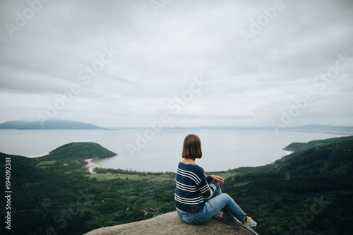 back view of young woman sitting on cliff and enjoying amazing landscape in Hai Van Pass, Vietnam