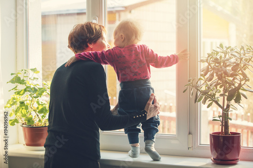 grandmother playing and taking care of child at home