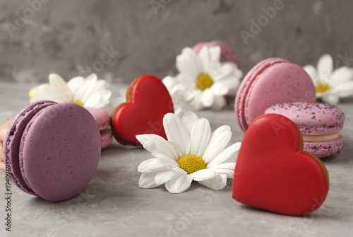 Plexiglas Macarons Flowers, colorful macarons, heart shaped cookies, gift box on grey background. Close-up.