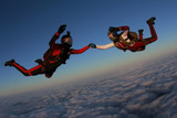 Two skydivers are in the winter sunset sky. - 194106360
